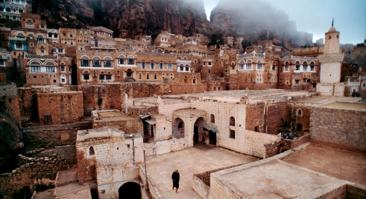 Character etched in every detail, Yemen shows its ancient face in the mountain village of At Tawilah, where the simplicity of the mosque stands in contrast to the colors and intricate designs of traditional Yemeni architecture.   Yemen United National Geographic, April 2000.
